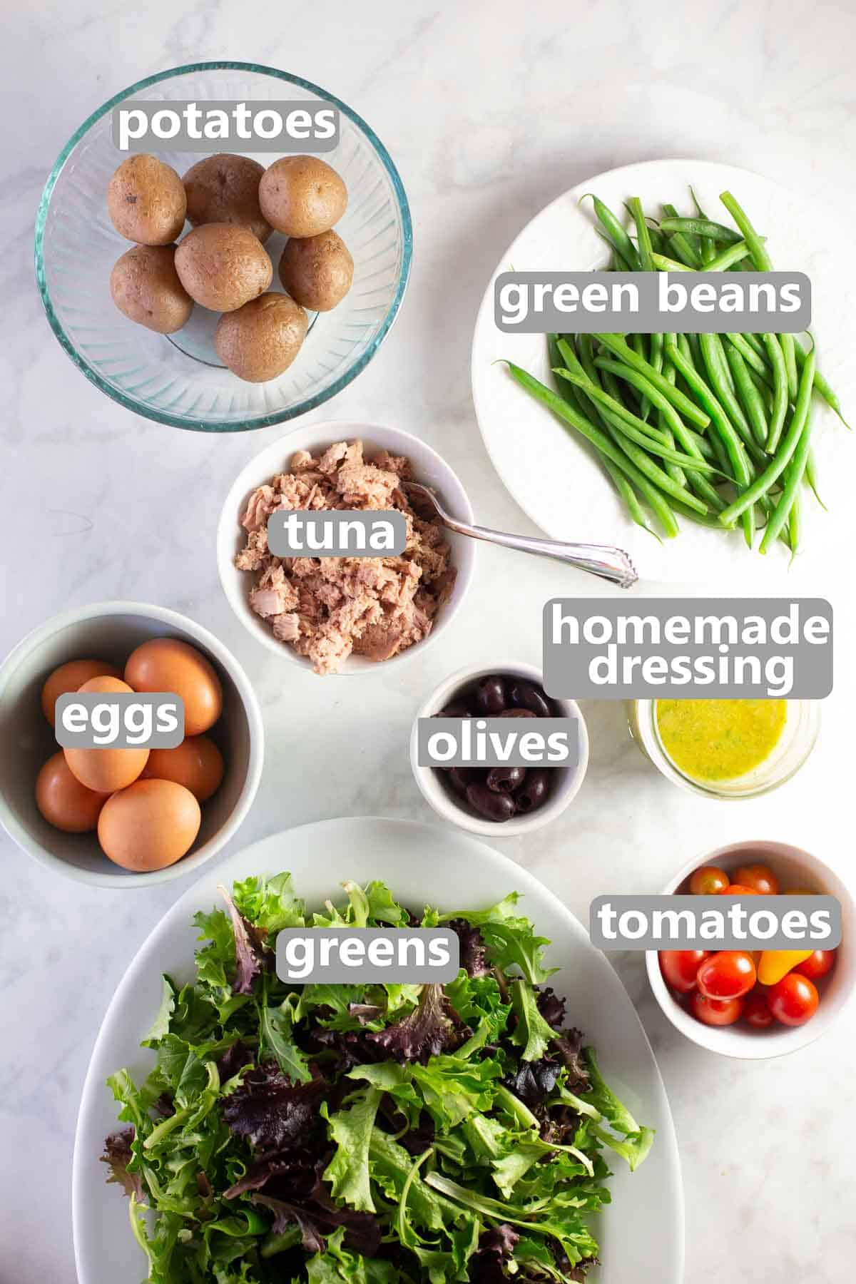 Salad nicoise ingredients - potatoes, green beans, tuna, eggs, olives, homemade dressing, spring greens and tomatoes