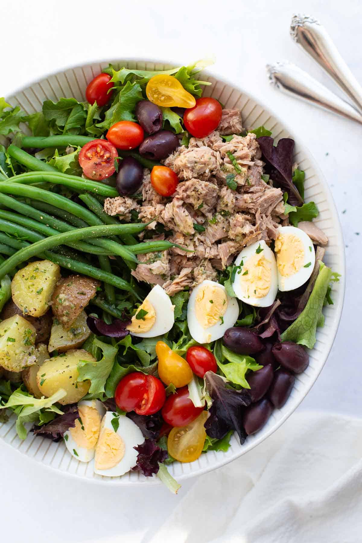 Salad nicoise with spring greens, potatoes, green beans, eggs, cherry tomatoes, tuna, olives and a fresh herb vinaigrette.