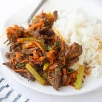 shot of beef stir fry on white plate with rice