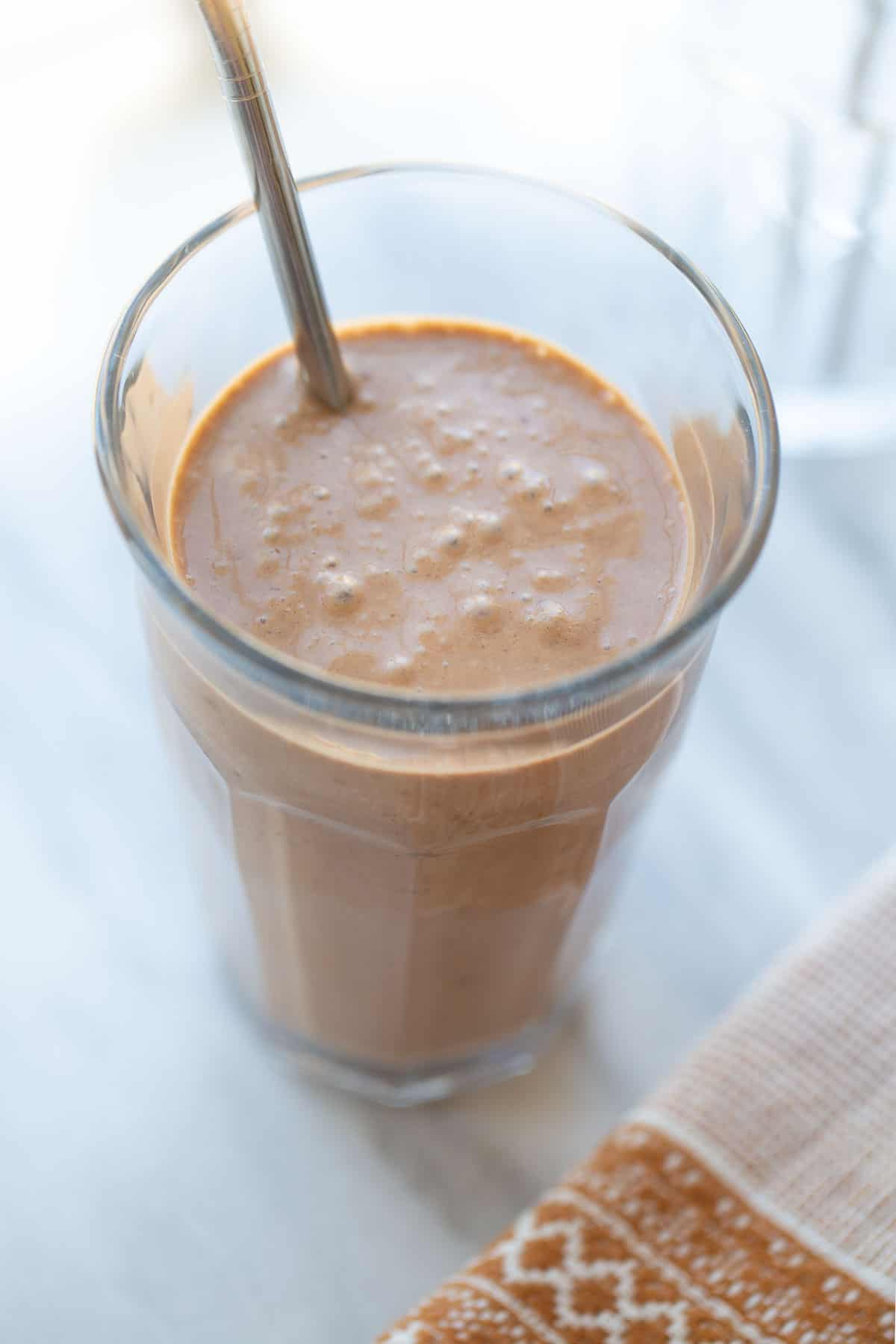 healthy chocolate smoothie with peanut butter and banana in a glass with a straw
