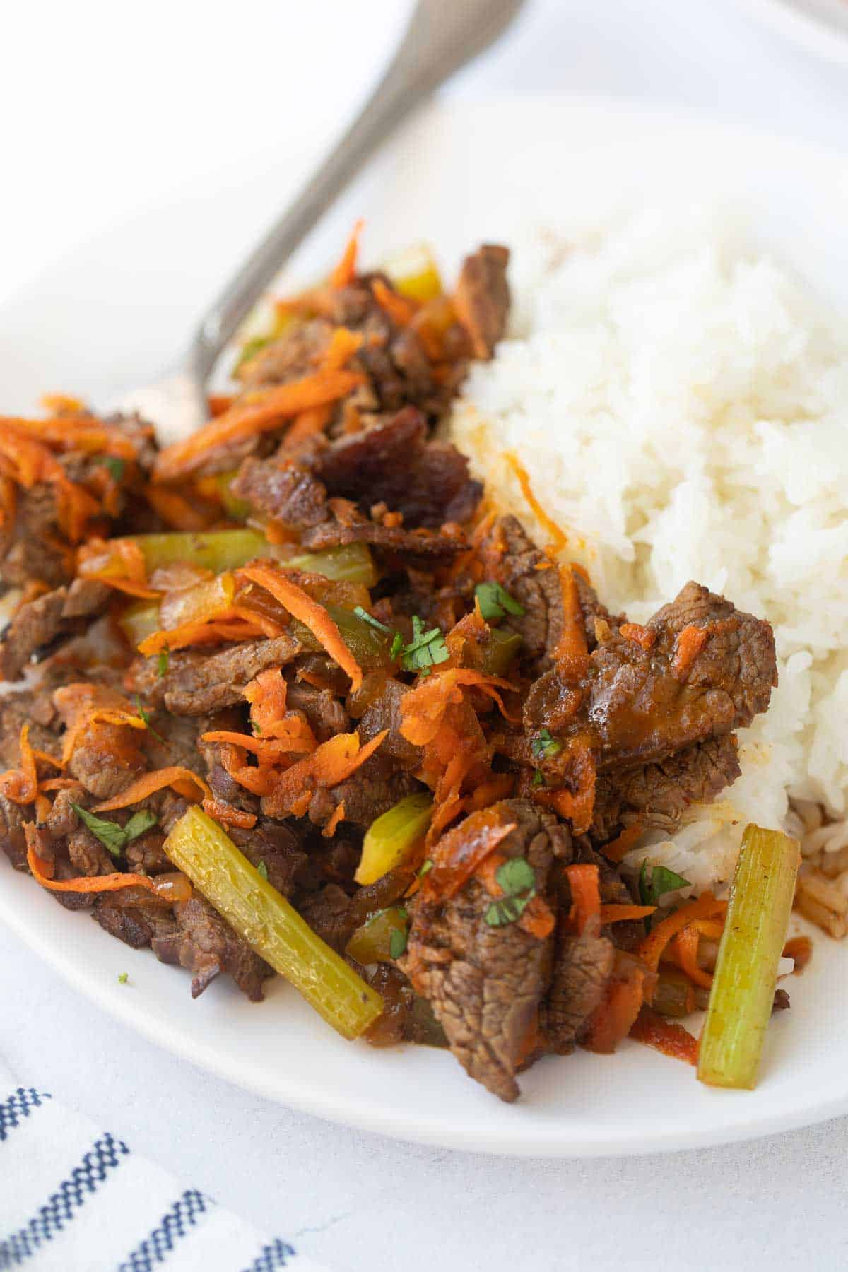 close up of thin slices of cooked flank steak, carrots and green peppers on bed of white rice.