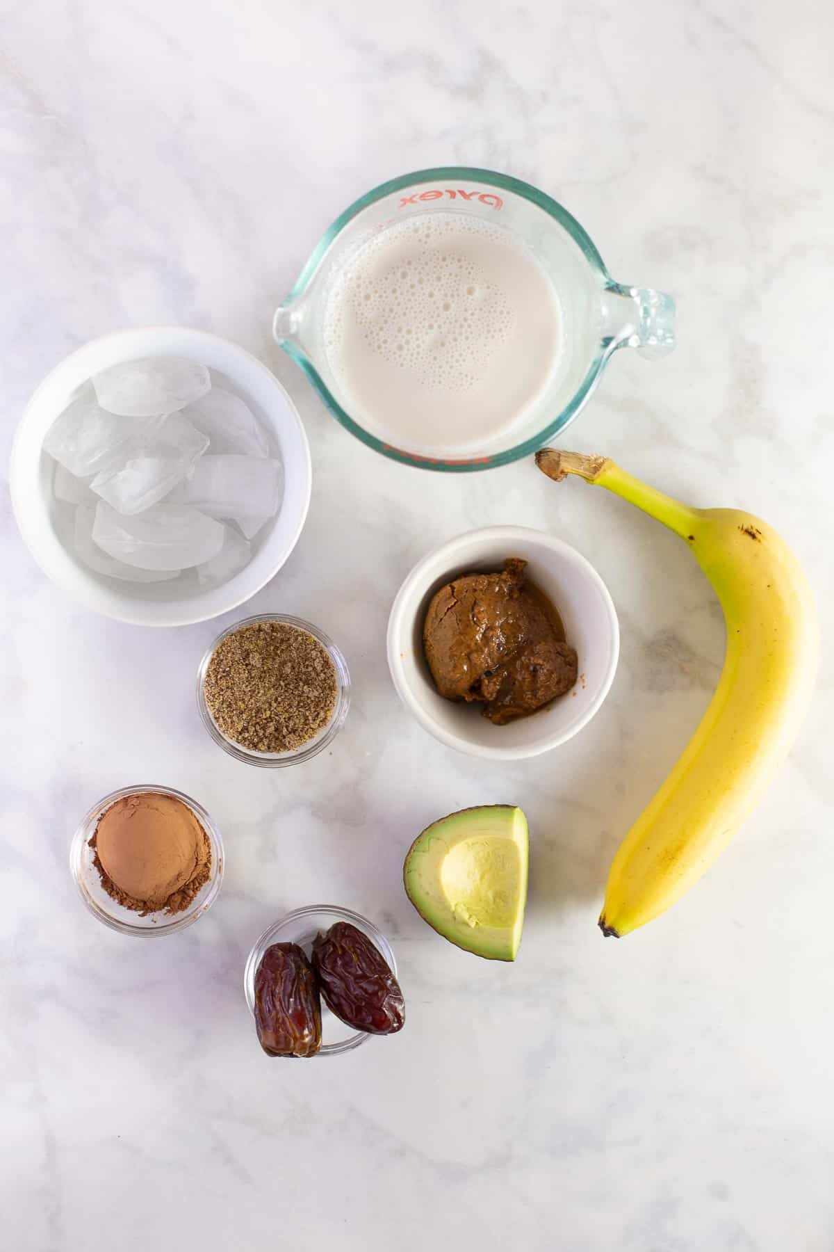ingredients needed to make a healthy breakfast drink with banana, chocolate and avocado
