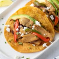 chicken fajita tacos on white plate