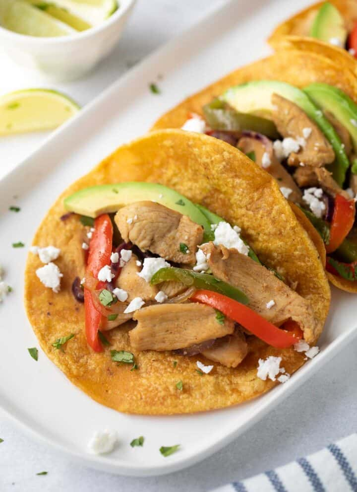easy chicken fajitas with cheese and avocado slices