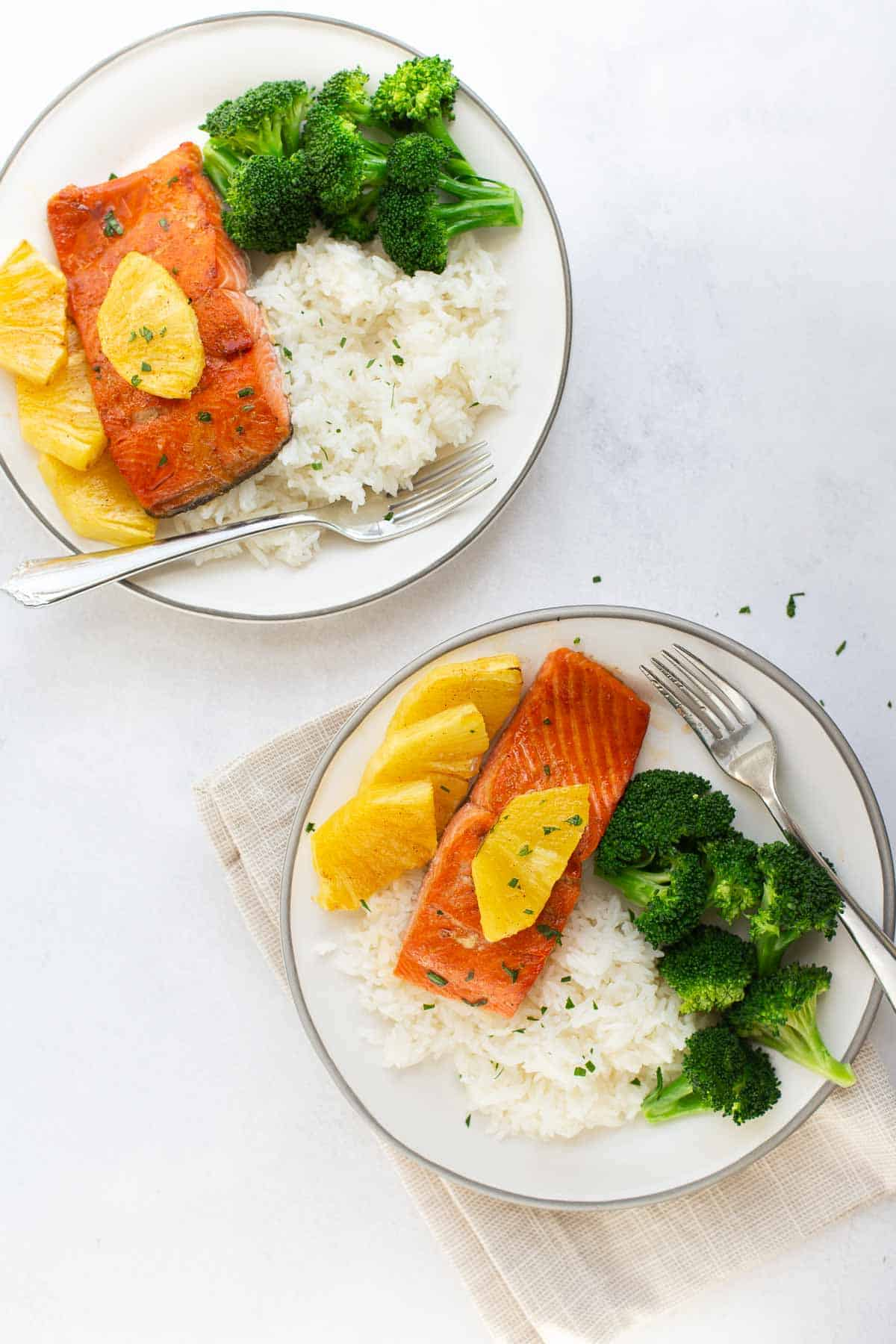 2 dinner plates of pineapple salmon with white rice and steamed broccoli