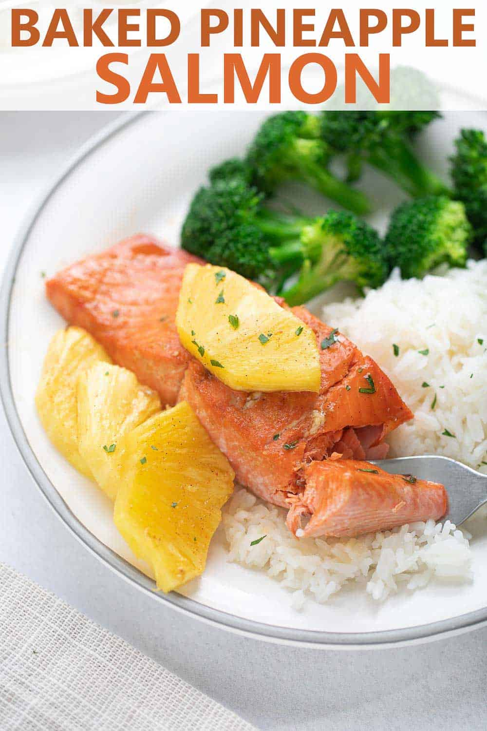 close up shot of baked salmon on white plate with pineapple and broccoli