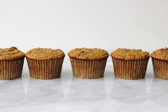 zucchini muffins lined up in a row on marble background
