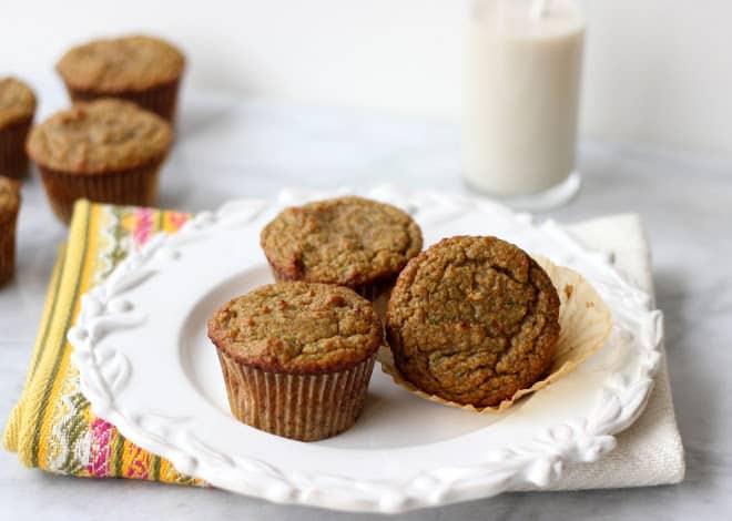 three paleo zucchini muffins on white plate with glass of milk
