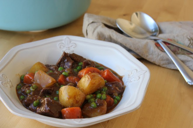 Bowl of beef stew with two spoons in the background