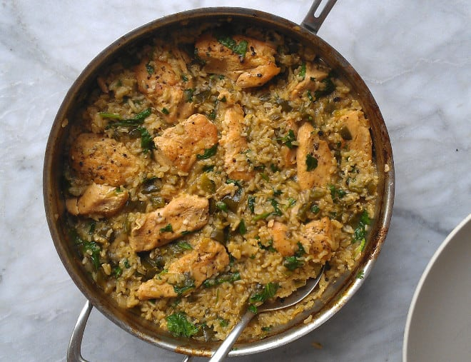 skillet chicken with mexican green rice in a pan with a spoon