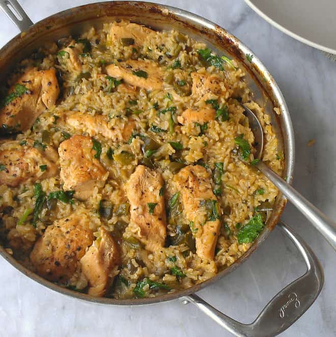 Skillet chicken and mexican green rice in a pan with a spoon