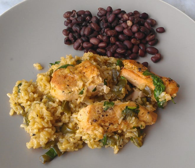 Skillet chicken over rice with beans on the side on a grey plate
