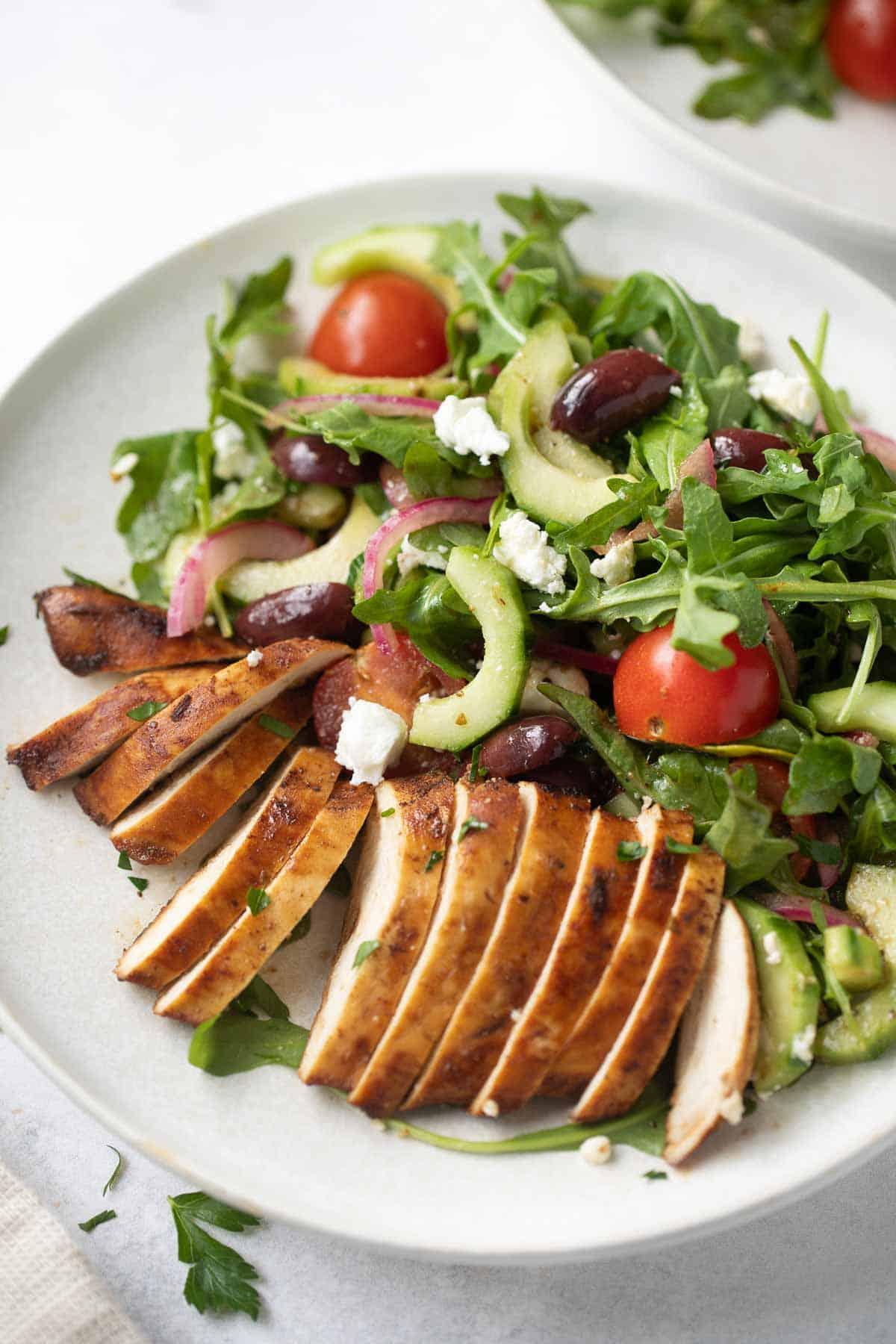 Greek chicken salad on round white dinner plate
