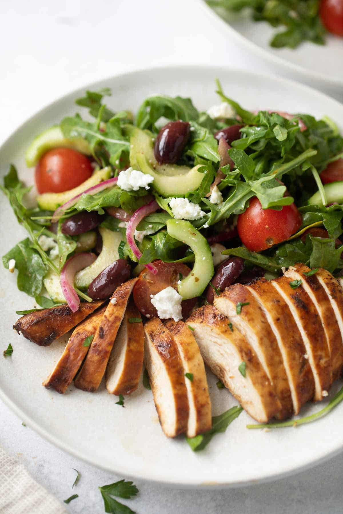 Mediterranean salad on a white plate with slices of grilled chicken breast