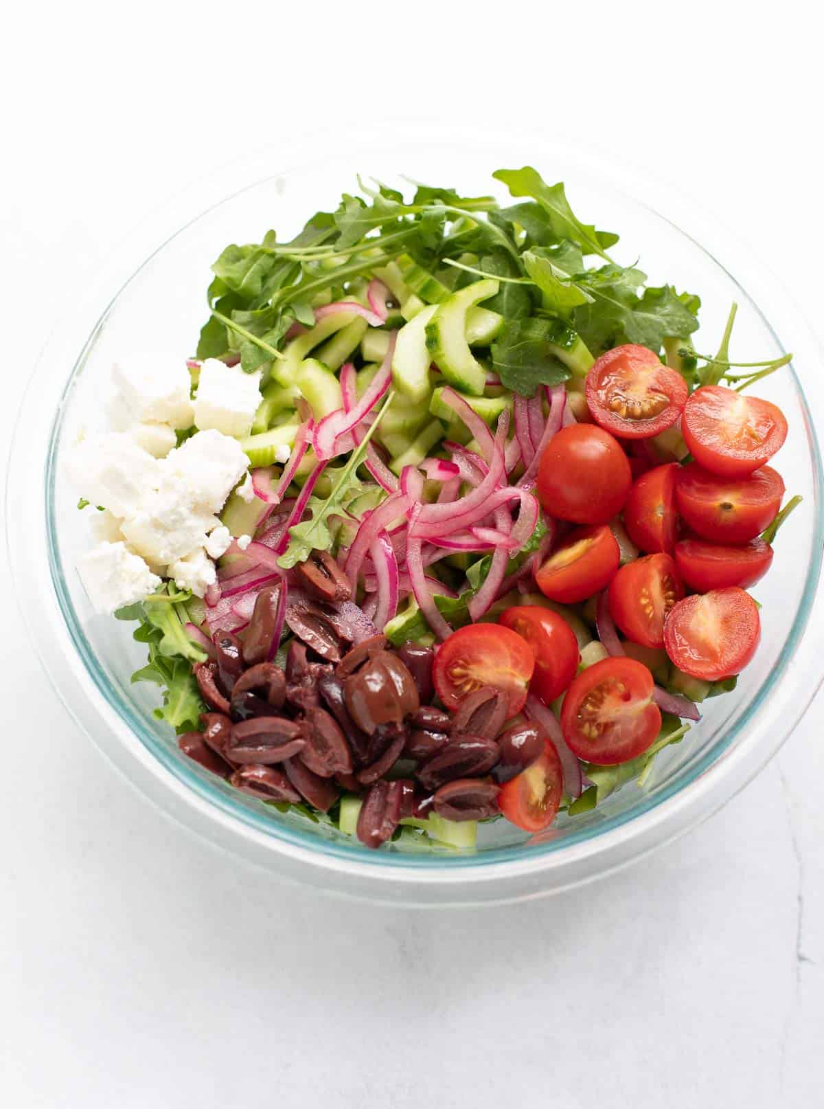 slices of cucumber, cherry tomatoes, kalamata olives, red onion, and arugula in large glass bowl