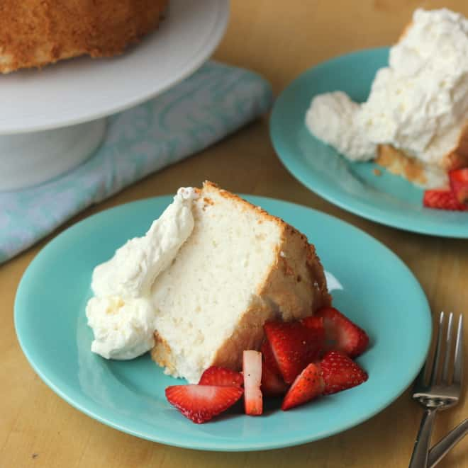 slice of angel food cake on blue plate with strawberries and whipped cream
