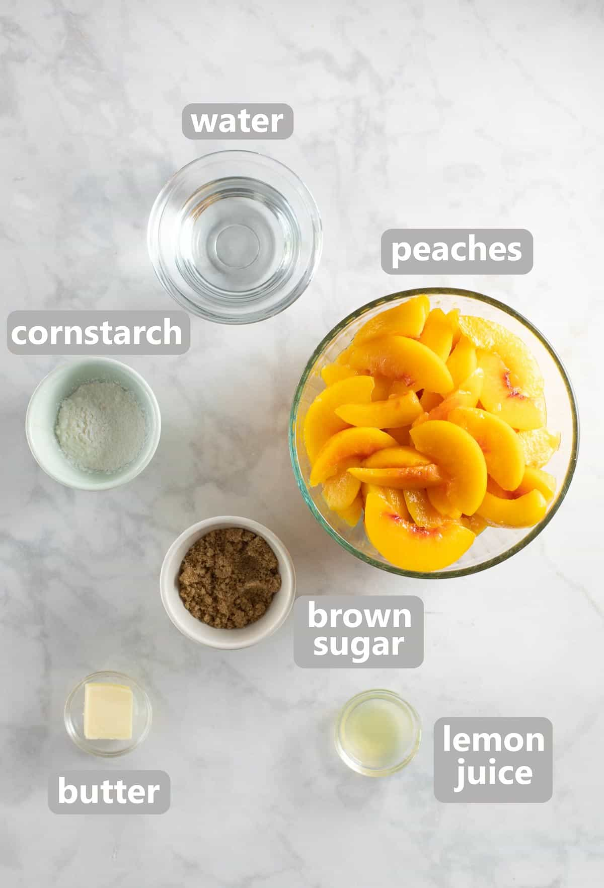 ingredients for peach cobbler filling in bowls on marble background