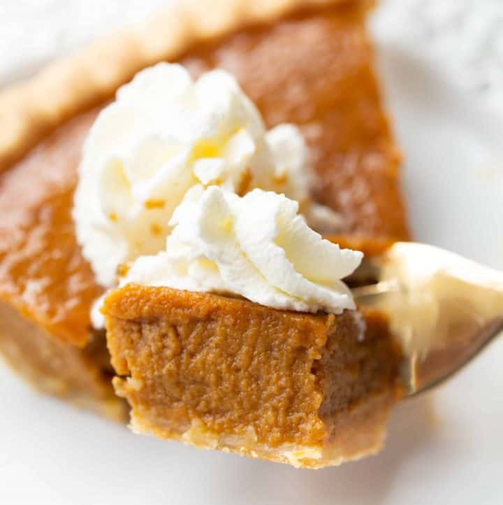 Slice of pumpkin pie with a piece on a fork
