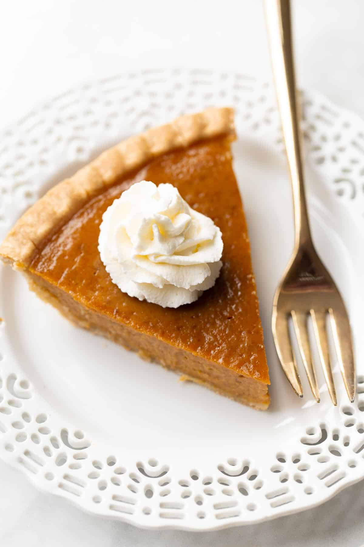 Slice of pumpkin pie topped with whipped cream next to a gold fork