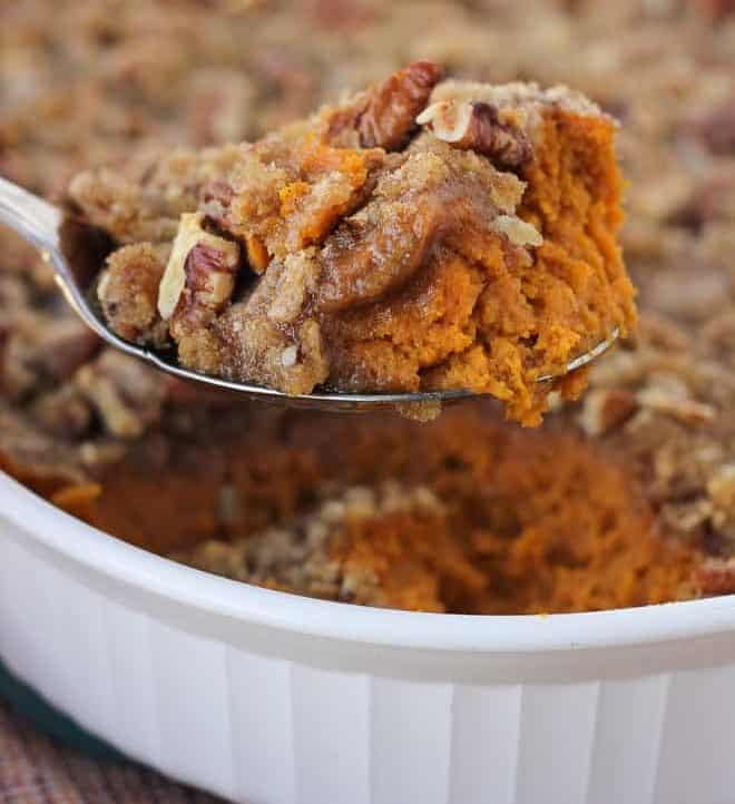 sweet potato casserole being scooped from white casserole dish with red and orange napkin