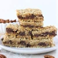 Sideview of a stack of caramel filled cookies on a white plate