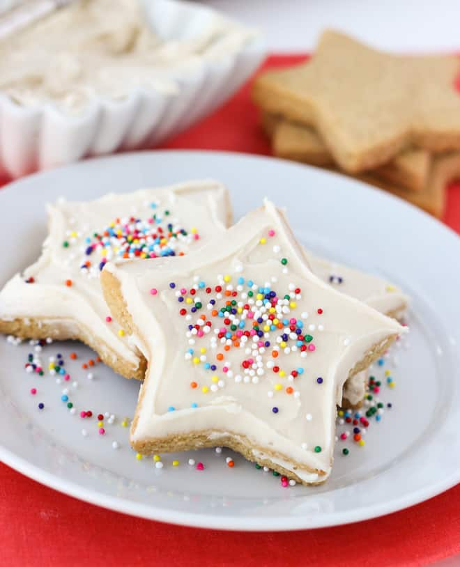 sugar cookies on white plate with sprinkles on pink napkin