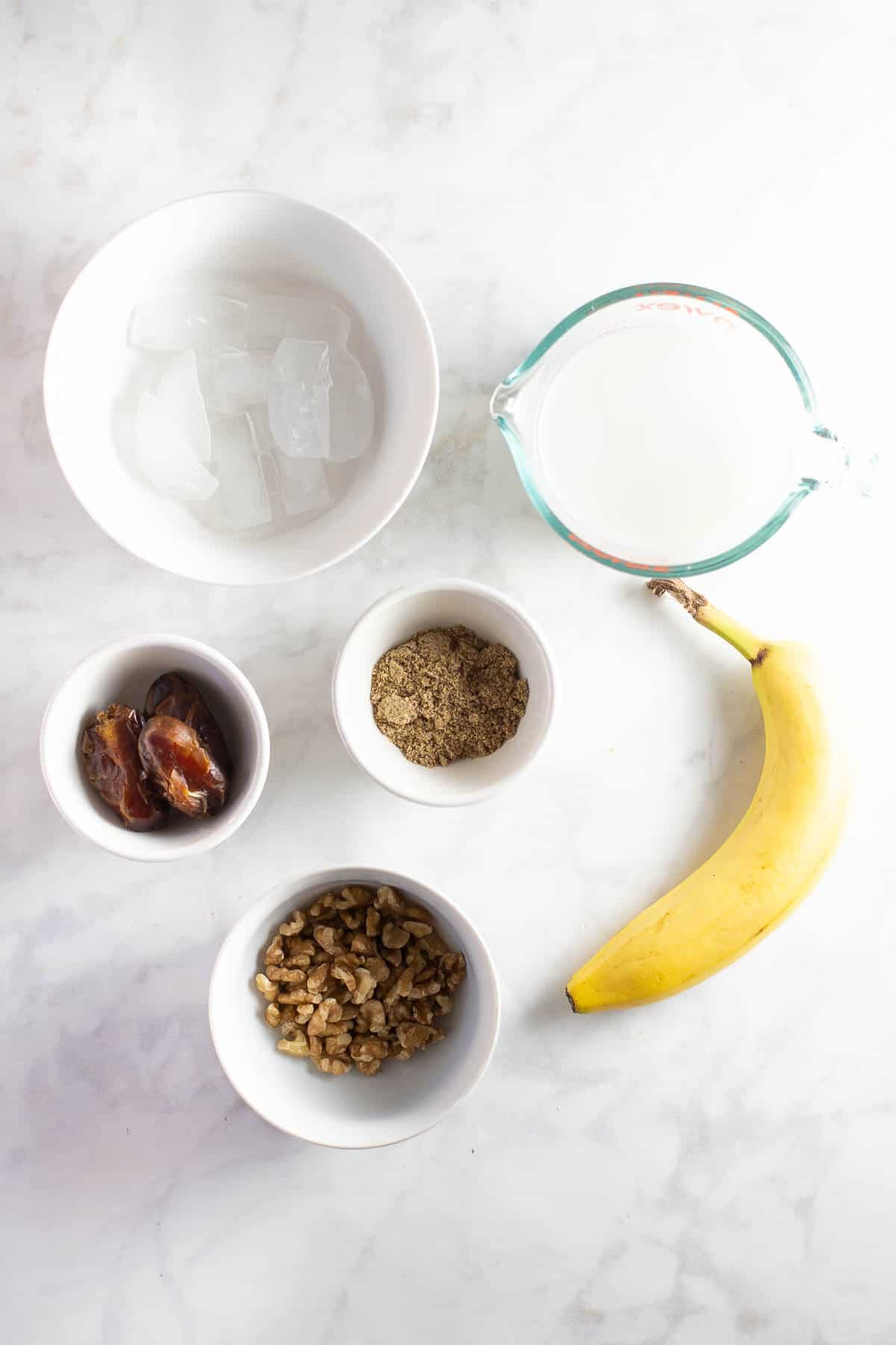 ingredients in white prep bowls to make a banana smoothie recipe