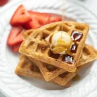 gluten free waffle on white plate with syrup