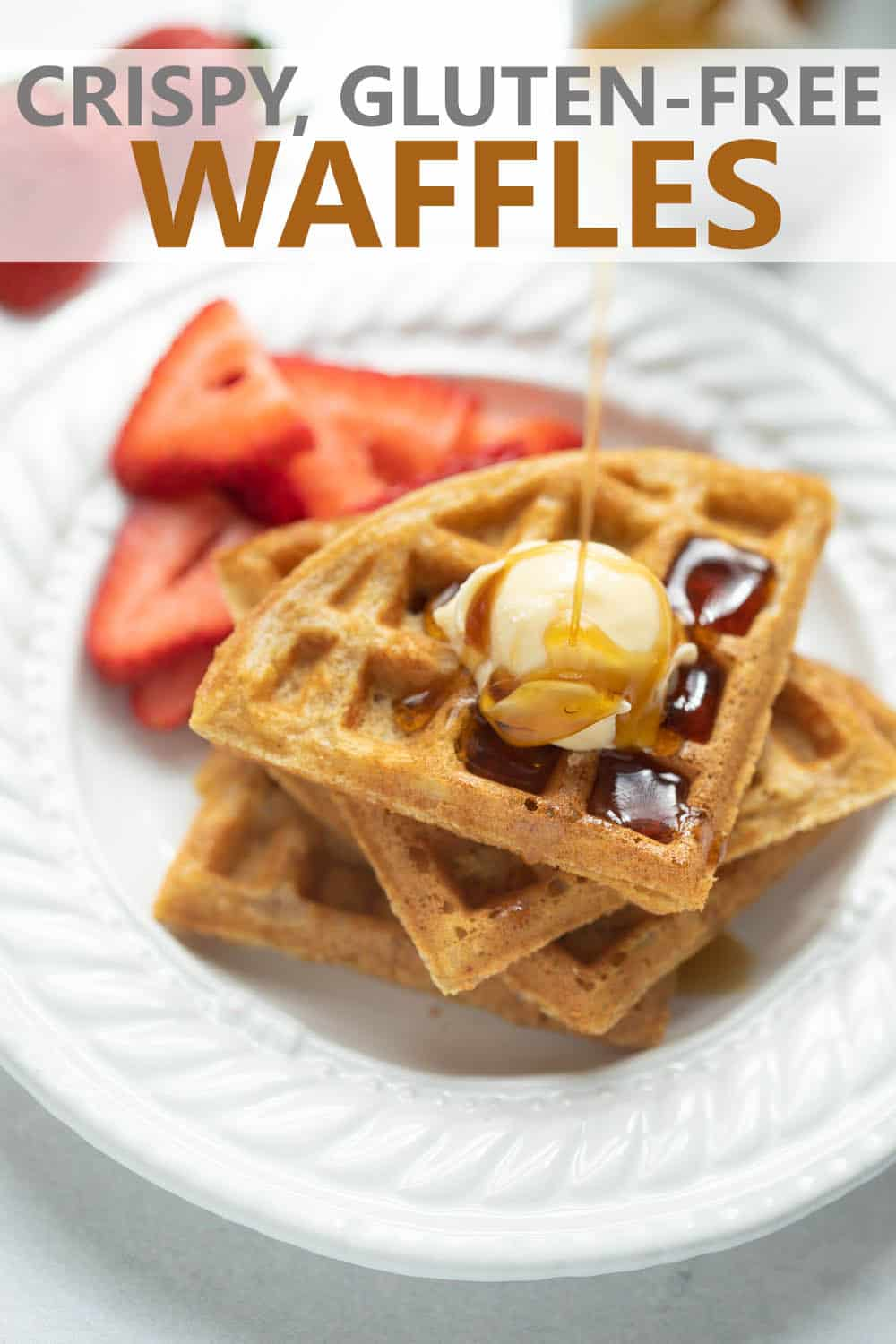 close up shot of waffles on white plate with maple syrup