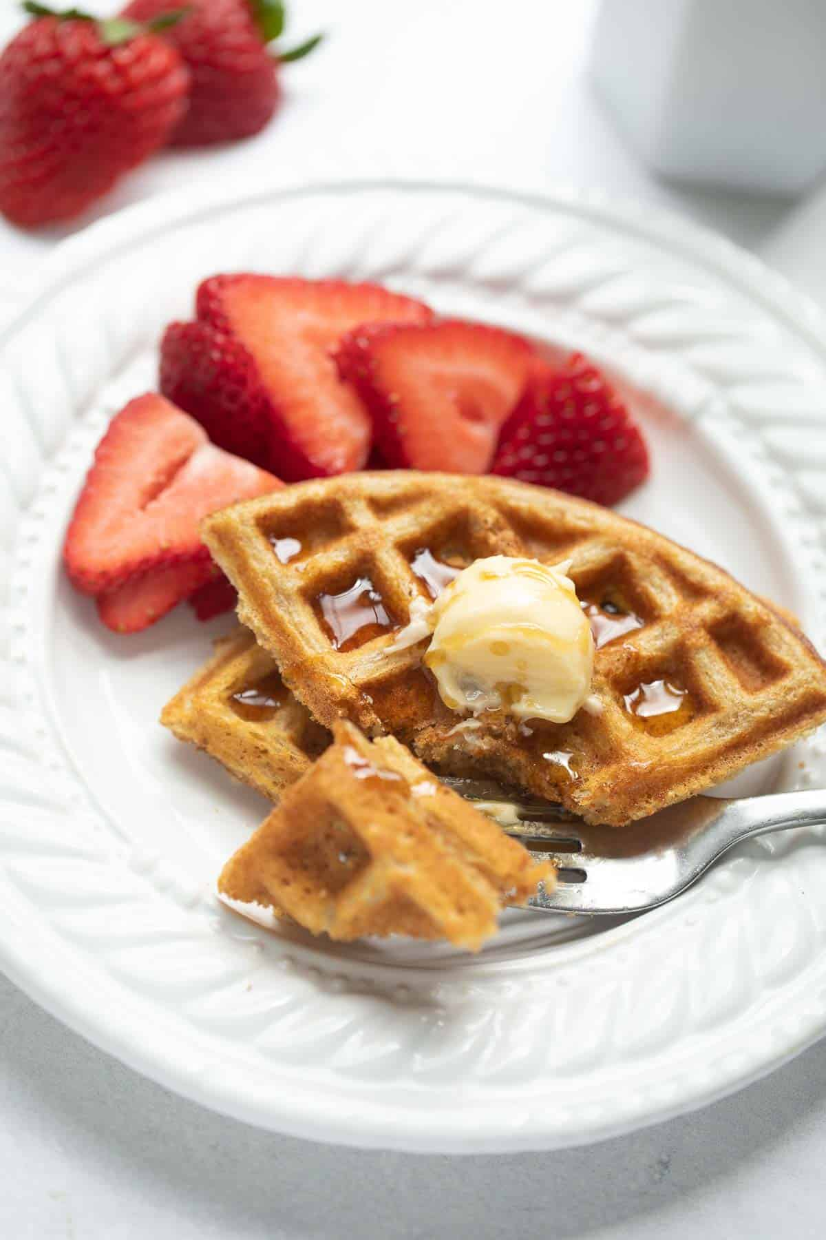 gluten free waffles on white plate cut with fork