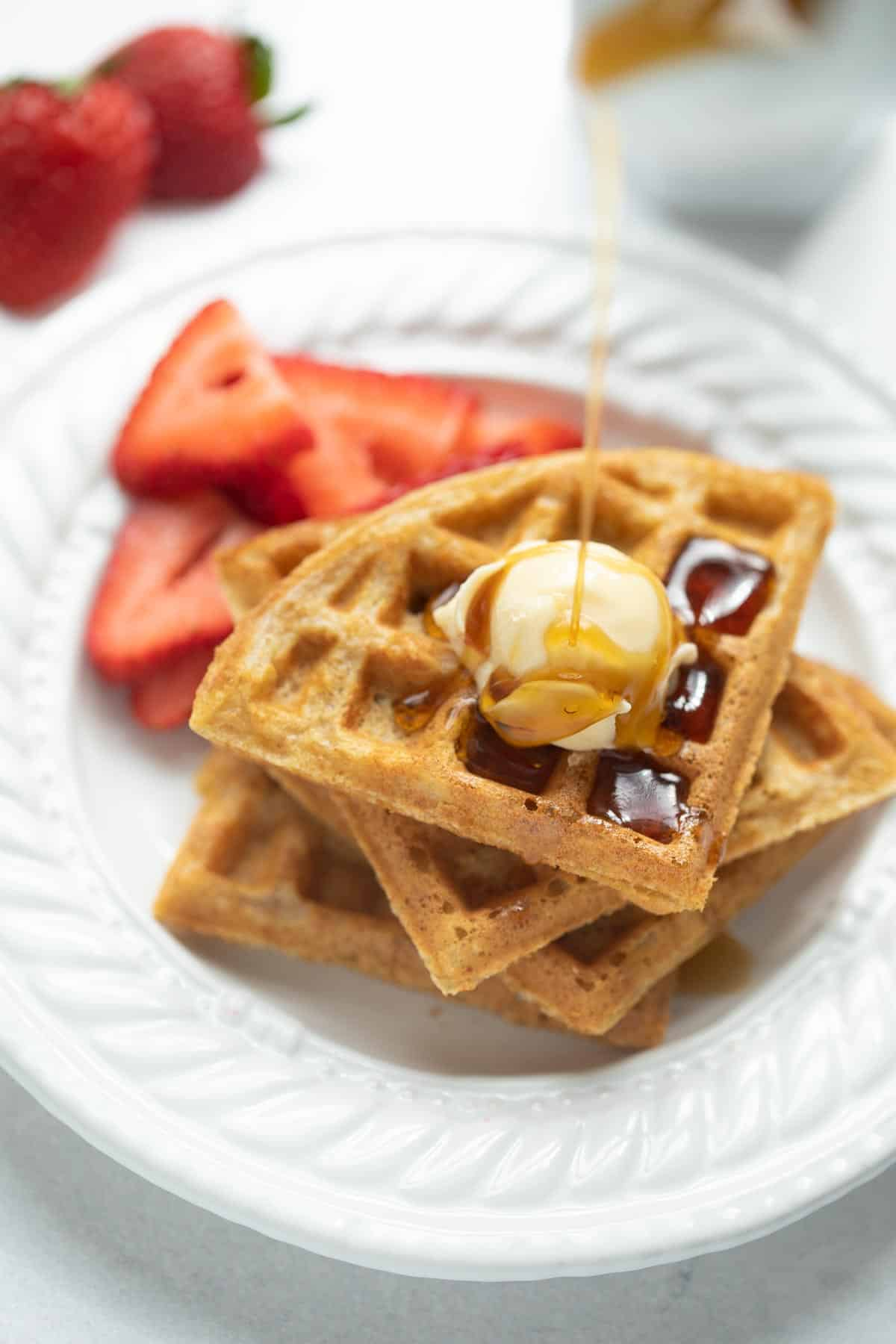 gluten free waffles with syrup and butter on a white plate
