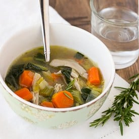 chicken soup in bowl with spoon and glass of water