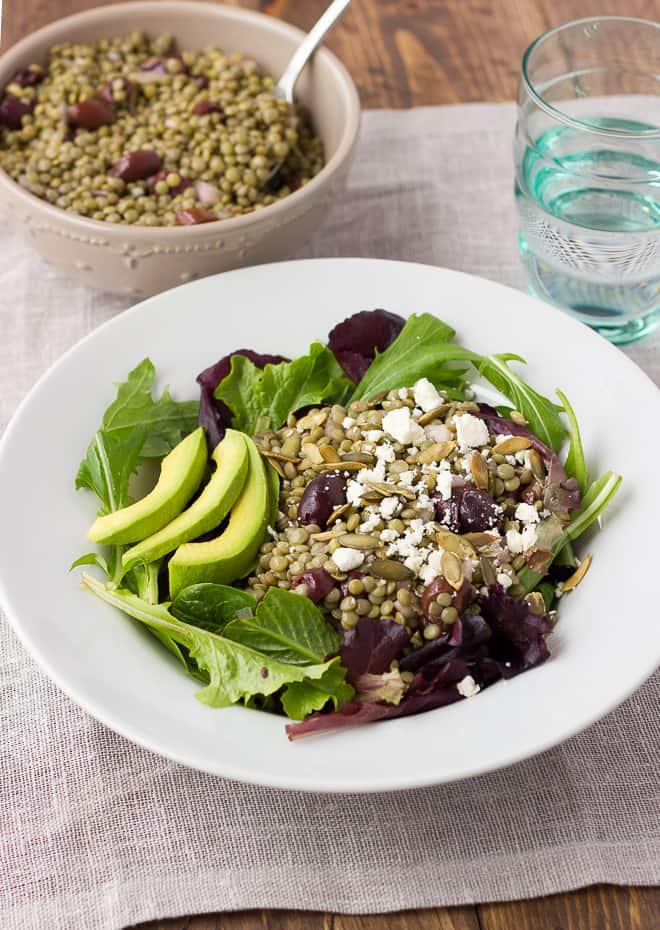 close up shot of lentil salad in white bowl over greens