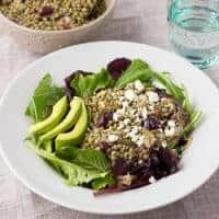 close up shot of lentil salad over greens in white bowl