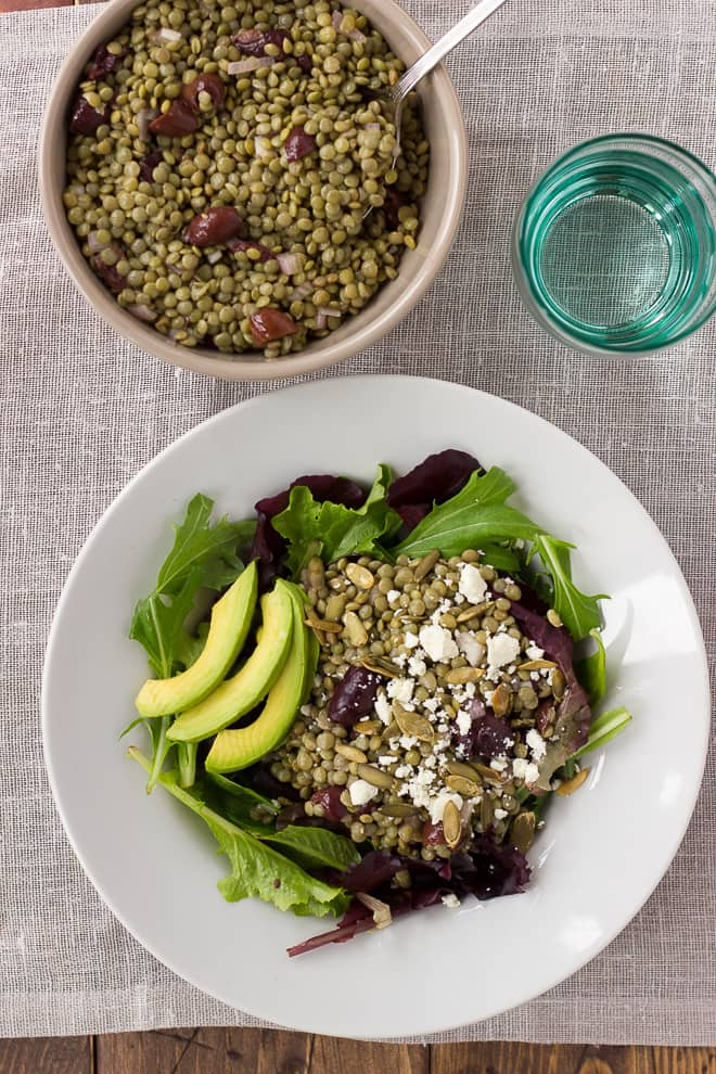 overhead shot of lentil salad and greens in white bowl