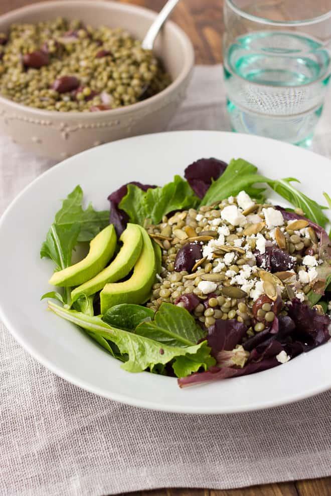 lentil salad over greens in white bowl