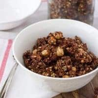 chocolate granola in white bowl with white and red dish towel