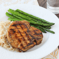 Honey-glazed pork chops with rice and asparagus on a white plate