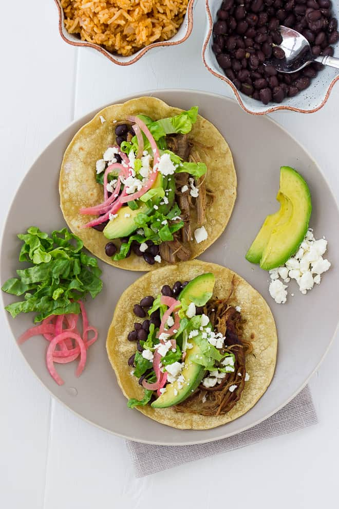 overhead shot of pork tacos with pickled onions and avocado on gray plate