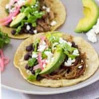 pork tacos topped with avocado and pickled onions