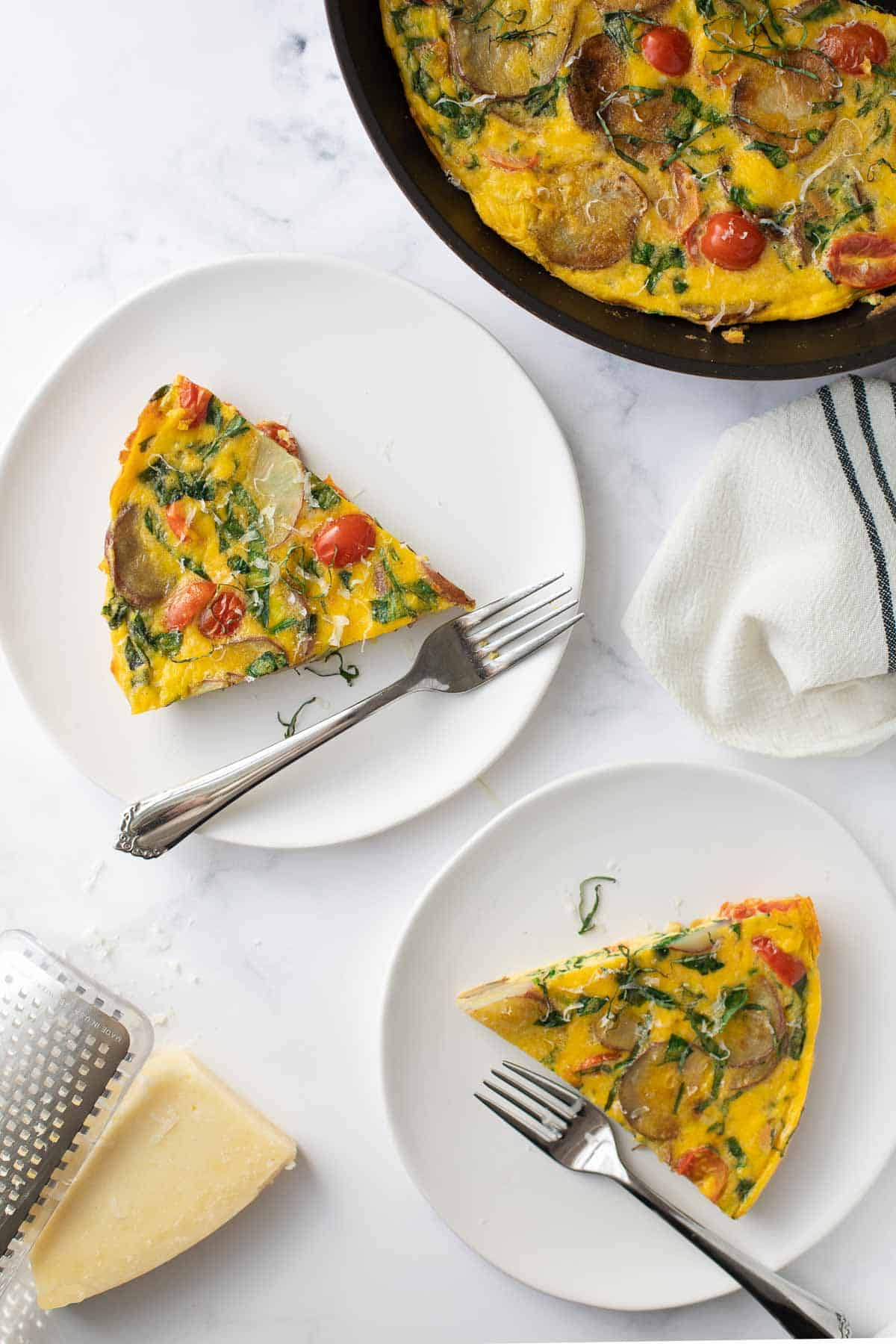2 plated servings of tomato, spinach and potato frittata with cheese