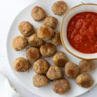 meatballs on white plate with bowl of marinara sauce