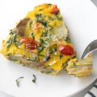 frittata on white plate topped with basil and fork