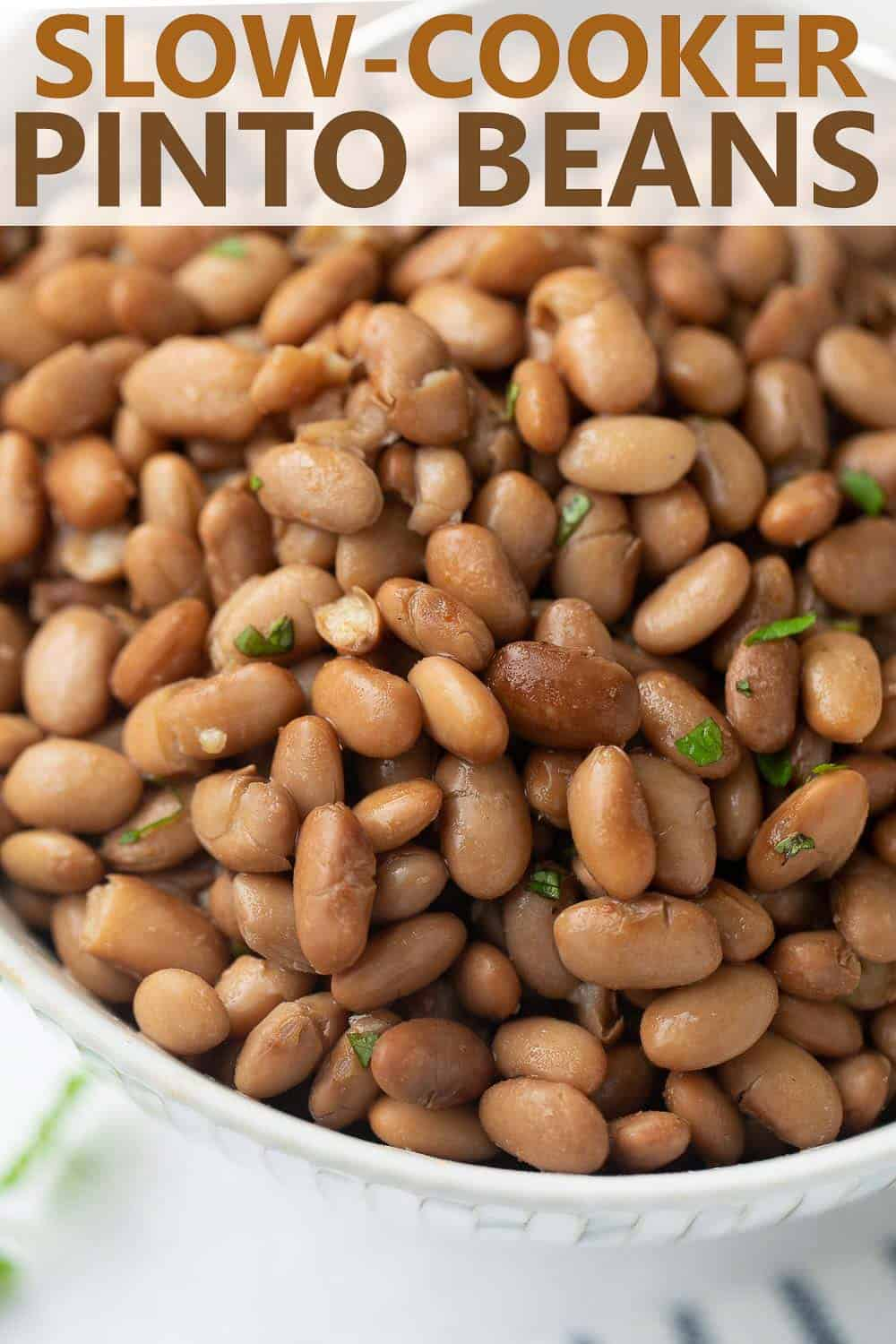 close up shot of cooked pinto beans in white bowl