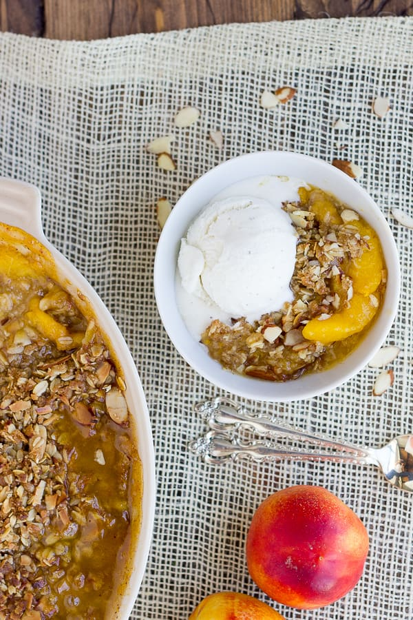 Gluten-Free Peach Crisp! A toasty, buttery topping made of oats and sliced almonds over warm, spiced peaches. Summer dessert heaven!