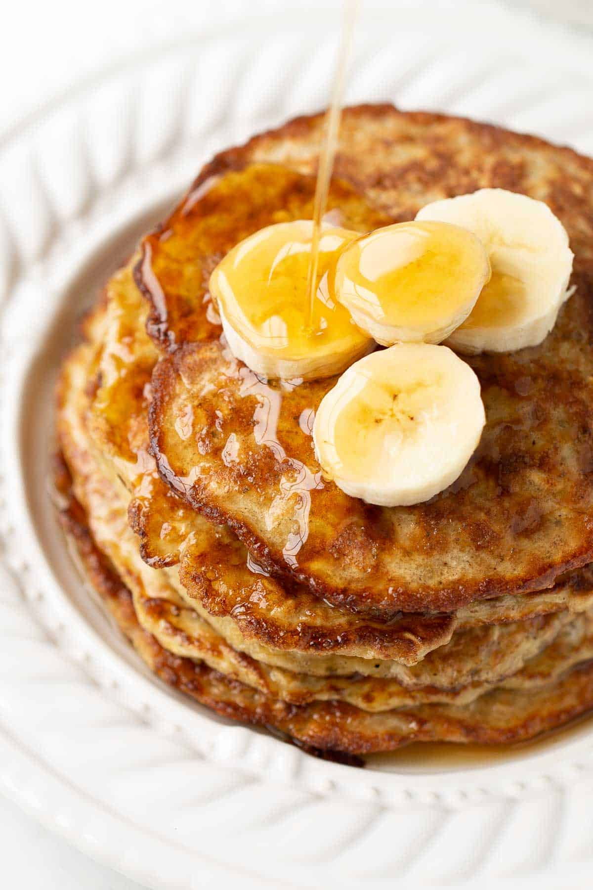 close up of banana pancakes on white plate