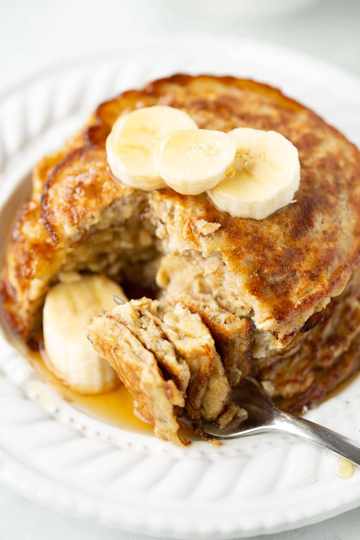 fork taking a bite of banana pancakes on a white plate