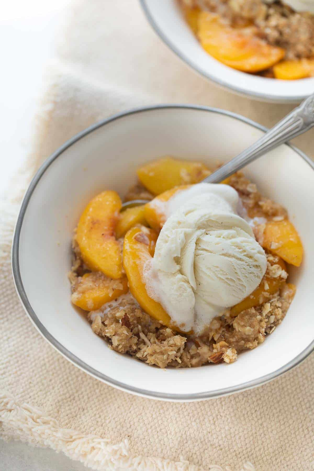 peach crisp in white bowl topped with ice cream and spoon