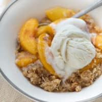 gluten-free peach crisp topped with vanilla ice cream in white bowl