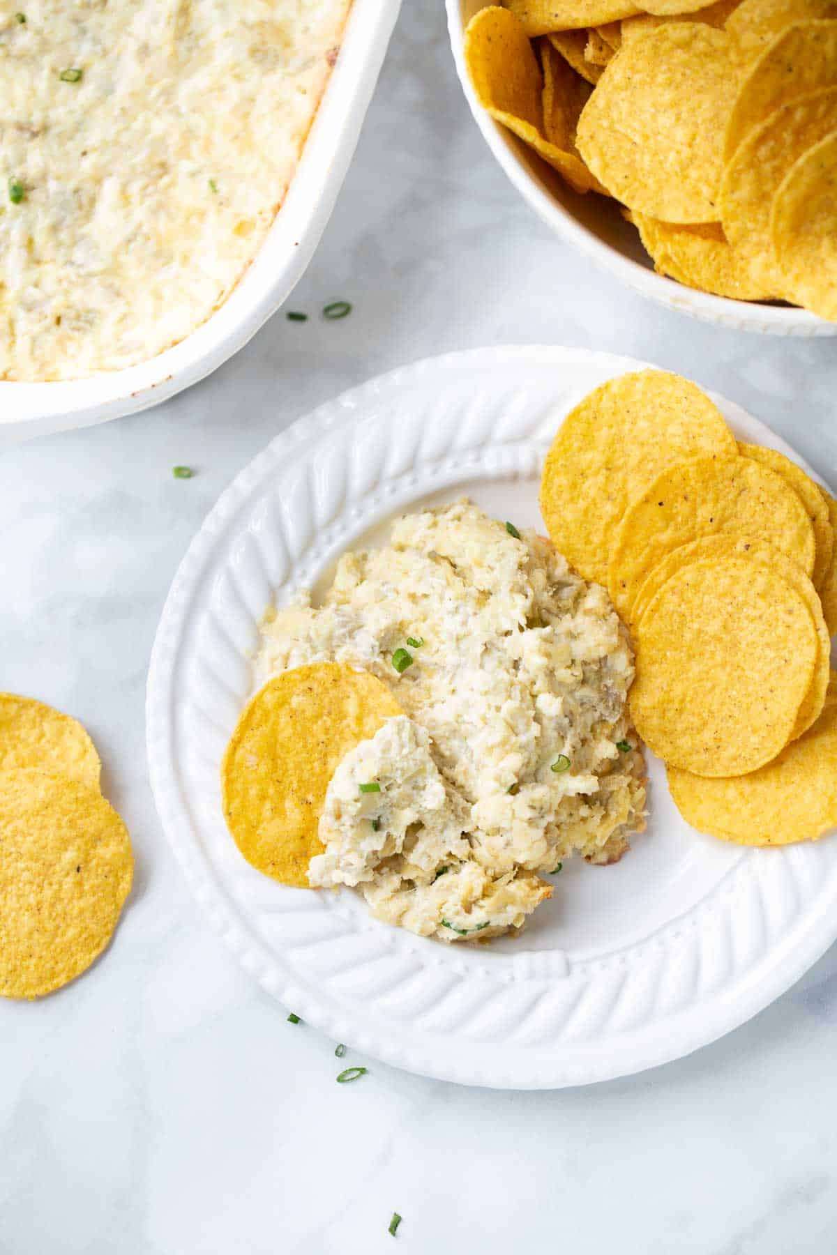 artichoke dip on white plate with tortilla chips for serving